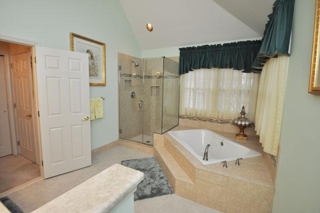 The Bathroom Added A Beautiful Glass Enclosed Shower And Roomy Step Up  Corner Bathtub