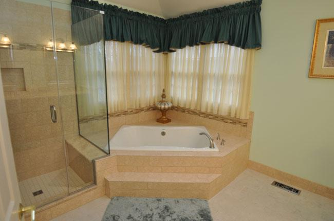 View from the hall into the bathroom corner tub and glass enclosed ...