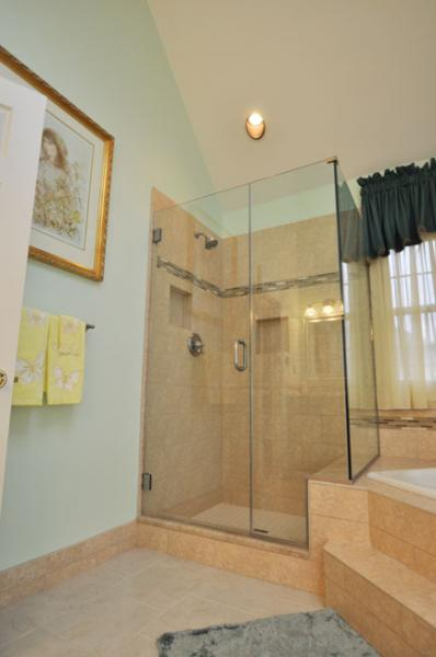 The roomy, glass enclosed shower also picks up the decorative tile ...