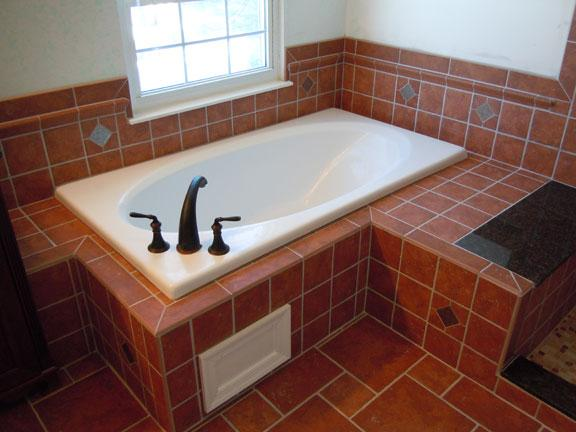 A new soaking tub with decorative tile work around the wall and an ...